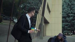Affärsman som går med tiggaren på gatan stock video