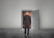 Affärsman som går in mot dörren som är öppen men blockeras av röd tegelsten w royaltyfria foton