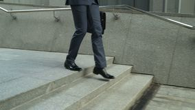 Affärsman som går ner trappa som ser smartphonen, slut av arbetsdags lager videofilmer