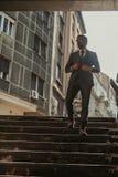 Affärsman som går ner trappan och innehavet hans omslag fotografering för bildbyråer