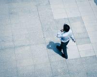 Affärsman som går och använder den smarta telefonen Arkivbilder