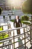 Affärsman som går på gatan på den soliga dagen Arkivfoto
