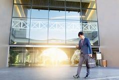 Affärsman som går på trappan och utomhus använder smartphonen royaltyfria foton