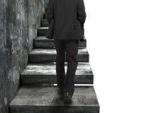 Affärsman som går upp den gamla konkreta trappan arkivfoton