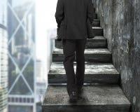 Affärsman som går upp den gamla konkreta trappan royaltyfri foto