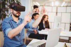 Affärsman som gör en gest, medan genom att använda virtuell verklighethörlurar med mikrofon Royaltyfria Foton