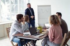 Affärsman som gör en presentation på kontoret Affärsledare som levererar en presentation till hans kollegor under arkivfoto