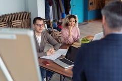 Affärsman som gör en presentation på kontoret Affärsledare som levererar en presentation till hans kollegor under royaltyfri foto