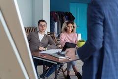 Affärsman som gör en presentation på kontoret Affärsledare som levererar en presentation till hans kollegor under arkivfoton