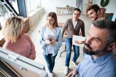 Affärsman som gör en presentation på kontoret Affärsledare som levererar en presentation till hans kollegor under fotografering för bildbyråer