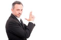Affärsman som gör en vapengest med handen arkivbilder