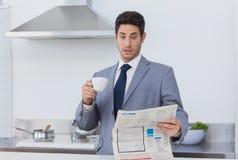 Affärsman som göras häpen, när läsa nyheterna arkivfoto