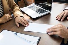 Affärsman som ger avsägelsebokstaven till personalresurschefen arkivfoto