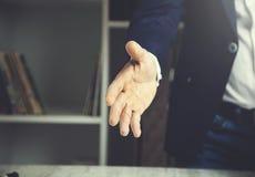 Affärsman som ger en hand royaltyfria bilder