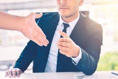 Affärsman som ger hans hand för handskakning till partnern, partnerskapteamwork eller det lyckade avtalsbegreppet fotografering för bildbyråer