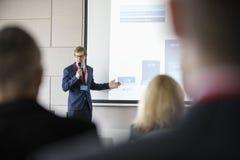 Affärsman som ger presentation i seminariumkorridor på konventcentret Royaltyfri Foto