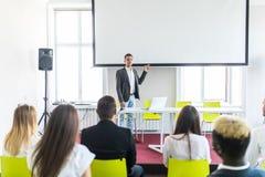 Affärsman som ger presentation till hans kollegor affären chairs konferensskrivbordet som isoleras över white nätverkande royaltyfri foto