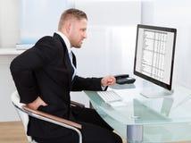 Affärsman som gnider hans baksida, som han sitter arbete på hans skrivbord Arkivfoto