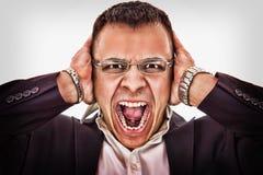 Affärsman som griper hans huvud och skrän Arkivbild