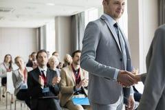 Affärsman som hälsar den offentliga högtalaren under seminarium royaltyfria foton