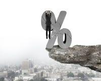 Affärsman som hänger på sprucket procentsatstecken med den stads- klippan Royaltyfria Foton