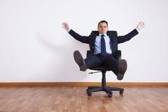 Affärsman som har gyckel med hans stol Royaltyfria Bilder
