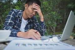 Affärsman som har huvudvärk, medan arbeta genom att använda bärbar datordatoren royaltyfria bilder