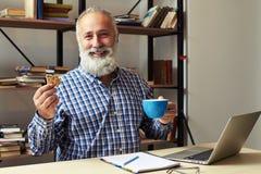 Affärsman som har kaffeavbrottet på hans arbetsplats royaltyfria bilder