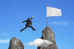 Affärsman som hoppar över bergmaximum till den tomma flaggan med himmel royaltyfria bilder