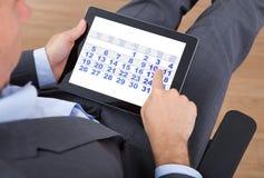 Affärsman som i regeringsställning använder kalendern på den digitala minnestavlan Arkivfoton