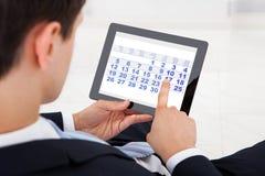 Affärsman som i regeringsställning använder kalendern på den digitala minnestavlan Fotografering för Bildbyråer