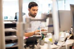 Affärsman som i regeringsställning använder mobiltelefonen på skrivbordet royaltyfri fotografi