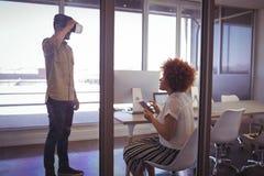 Affärsman som i regeringsställning använder VR-exponeringsglas med affärskvinnan royaltyfria foton