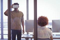 Affärsman som i regeringsställning bär VR-hörlurar med mikrofon med den kvinnliga kollegan Royaltyfri Fotografi