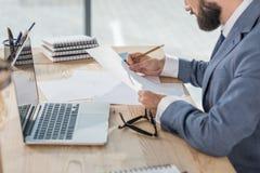 Affärsman som i regeringsställning gör skrivbordsarbete på arbetsplatsen Arkivbilder