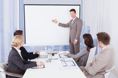 Affärsman som i regeringsställning ger presentation till kollegor arkivfoto