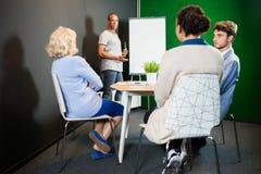 Affärsman som i regeringsställning ger presentation till kollegor Arkivfoton