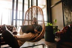 Affärsman som i regeringsställning kopplar av vardagsrummet under avbrott Arkivfoto
