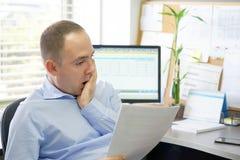 Affärsman som i regeringsställning läser en workspace för dokument royaltyfri foto