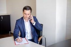 Affärsman som i regeringsställning talar på mobiltelefonen royaltyfri fotografi