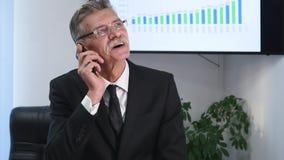 Affärsman som i regeringsställning talar på telefonen framme av skrivbordet lager videofilmer