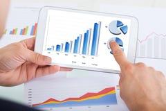Affärsman som jämför grafer på den digitala minnestavlan på kontorsskrivbordet Royaltyfri Foto