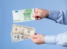 Affärsman som jämför hundra dollar och hundra euro Royaltyfri Foto