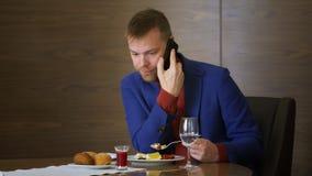 Affärsman som kallar till mobiltelefonen under att äta matställen i lyxig restaurang lager videofilmer