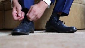 Affärsman som klär upp med klassikern, eleganta skor Ansa att bära på bröllopdag, snör åt band och att förbereda sig stock video