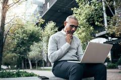 Affärsman som klarar av affären som arbetar på sammanträde för bärbar datordator royaltyfria bilder