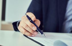 Affärsman som läser det uthyrnings- avtalet, innan framställning av ett avtal Företags man med pennan i handen som arbetar i mode royaltyfri fotografi