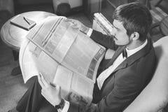 Affärsman som läser en tidning på kafét som sörjer Royaltyfri Foto