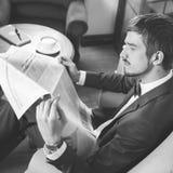Affärsman som läser en tidning på kafét som sörjer Arkivfoton