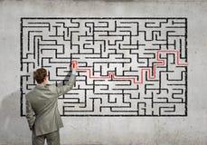 Affärsman som löser labyrintproblem Arkivfoto